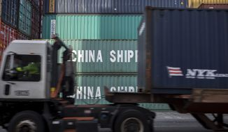 "In this Thursday, July, 5, 2018, photo, a jockey truck passes a stack of 40-foot China Shipping containers at the Port of Savannah in Savannah, Ga. The United States and China launched what Beijing called the ""biggest trade war in economic history"" Friday, July 6, imposing tariffs on billions of dollars of each other's goods amid a spiraling dispute over technology. (AP Photo/Stephen B. Morton)"