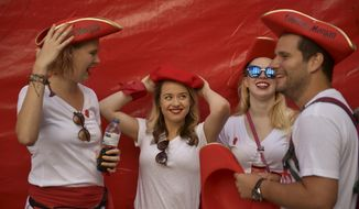 Revellers get ready for the launch of the 'Chupinazo' rocket, to celebrate the official opening of the 2018 San Fermin fiestas with daily bull runs, bullfights, music and dancing in Pamplona, Spain, Friday July 6, 2018. (AP Photo/Alvaro Barrientos)