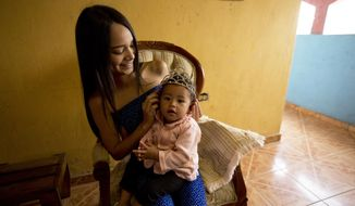 In this July 1, 2018 photo, Johandrys Colls places a crown on her niece Victoria, at her home, at a slum in the outskirts of Caracas, Venezuela. Colls' parents have enrolled her in one of Venezuela's top modeling schools despite their modest income in hopes of transforming their daughter into a sought-after beauty queen. (AP Photo/Fernando Llano)