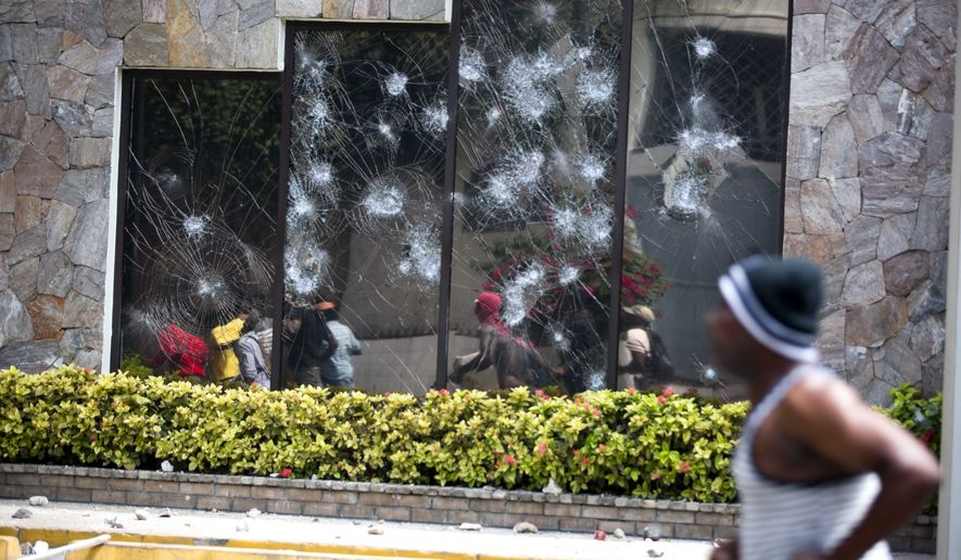 People move past the Best Western hotel during a protest over the cost of fuel in Port-au-Prince, Haiti, Saturday, July 7, 2018. The Haitian government suspended a fuel price hike Saturday hours after demonstrators attacked a Best Western Premiere hotel in one of the wealthiest neighborhoods of the capital. (AP Photo/Dieu Nalio Chery)