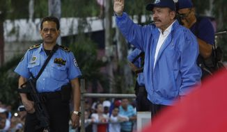 Escorted by one of his armed security guards, Nicaraguan President Daniel Ortega, right, waves to a crowd of party faithful during a march for peace, in Managua, Nicaragua, Saturday, July 7, 2018. According to Nicaraguan human rights groups more than 300 persons have been killed since ant-government protests started more than two months ago. (AP Photo/Alfredo Zuniga)