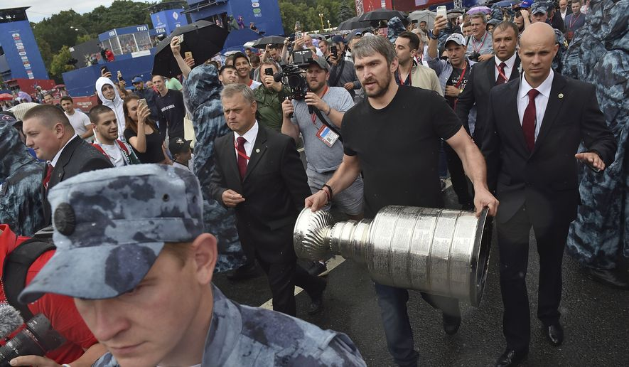"Washington Capitals Alex Ovechkin, from Russia, holds the Stanley Cup trophy at the fan zone in Moscow ahead of the the quarterfinal match between Russia and Croatia at the 2018 soccer World Cup that is being played in the Fisht Stadium, in Sochi, Russia, Saturday, July 7, 2018. Ovechkin is bringing the Stanley Cup to the World Cup. Fresh off winning the NHL title, the Washington Capitals forward is taking the trophy to Moscow on Saturday, where it will be exhibited at a ""fan fest"" public viewing site ahead of Russia's quarterfinal game against Croatia. (AP Photo/Dmitry Serebryakov) ** FILE **"