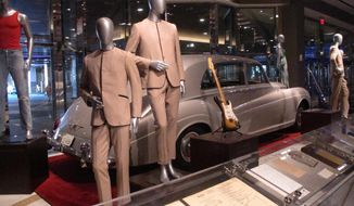 This July 5, 3018 photo shows suits worn by the Beatles during an early tour of America in front of the Rolls Royce automobile owned by Elvis Presley, part of a large collection of music memorabilia on display at the Hard Rock casino in Atlantic City, N.J. (AP Photo/Wayne Parry)