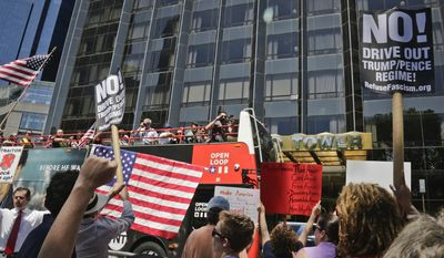 """Protesters rally outside a Trump hotel to call for the impeachment of President Trump, Sunday July 2, 2017, in New York. A statement from the organizer's website said President Trump """"has been in blatant violation of the Constitution"""" and that the House of Representatives has the power to impeach him. (AP Photo/Bebeto Matthews)"""