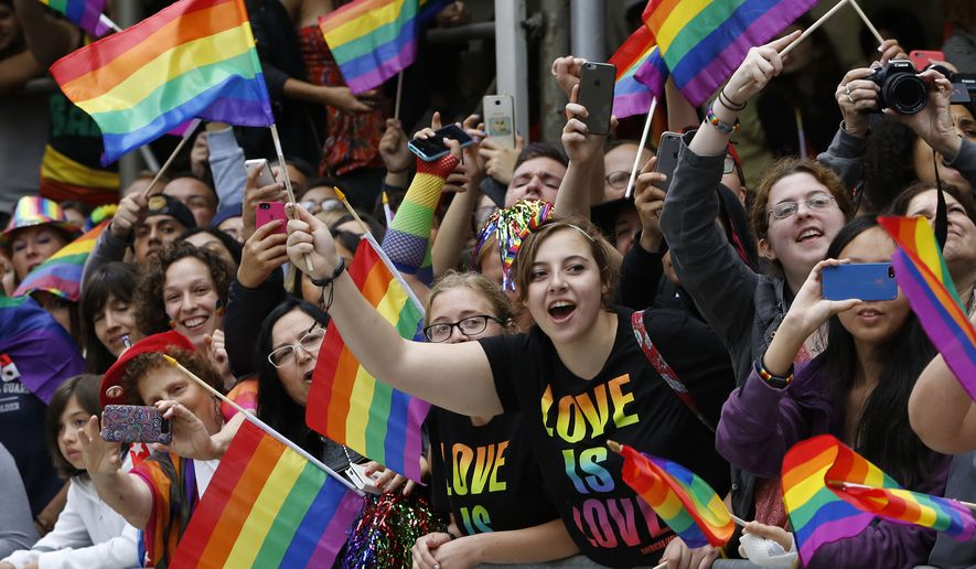 FILE - In this June 28, 2015 file photo, crowd waves rainbow flags during the Heritage Pride March in New York. Tennis legend Billie Jean King will be one of the grand marshals of New York City's gay pride march as cities around the world hold LGBT pride events. New York's march will pass by the Stonewall National Monument in Greenwich Village on Sunday, June 24, 2018, before heading up Fifth Avenue. (AP Photo/Kathy Willens, File)