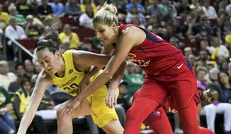 Seattle Storm forward Breanna Stewart, left, and Washington Mystics guard Elena Delle Donne dive for a loose ball in the first half of a WNBA basketball game, Sunday, July 8, 2018, in Seattle. Seattle won 97-91. (Bettina Hansen/The Seattle Times via AP) ** FILE **
