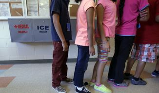 """FILE - In this Sept. 10, 2014 file photo, detained immigrant children line up in the cafeteria at the  Karnes County Residential Center,  a temporary home for immigrant women and children detained at the border, in Karnes City, Texas. Homeland Security Secretary Jeh Johnson says federal officials are making """"substantial changes"""" to end the long-term detention of migrant families who are being held mainly at two large facilities in Texas. (AP Photo/Eric Gay, File)"""