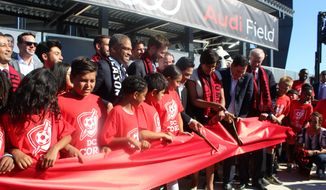Muriel Bowser, the mayor of Washington, D.C., is joined by D.C. United CEO Jason Levien, D.C. Council member Jack Evans and children from the D.C. Scores community program in cutting a ceremonial ribbon outside Audi Field, the new Major League Soccer stadium, on Monday, July 9, 2018. (Photo by Adam Zielonka / The Washington Times)