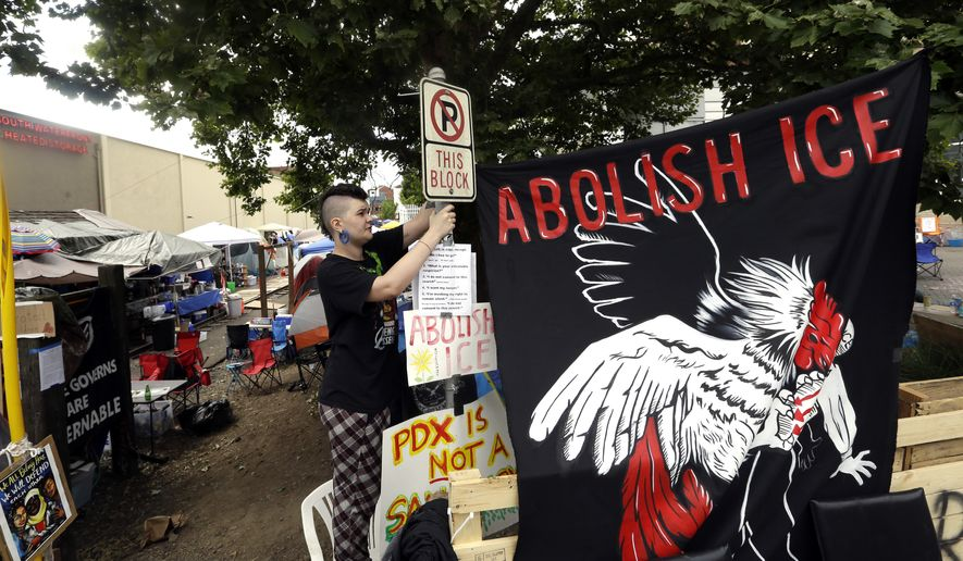 In this June 25, 2018, file photo, a woman, who would not identify herself, hangs a sign at a protest camp on property outside the U.S. Immigration and Customs Enforcement office in Portland, Ore. (AP Photo/Don Ryan, File)