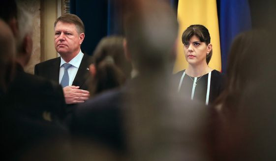 In this Thursday, Feb. 23, 2017 file photo, Romania's head of the anti-graft agency (DNA) Laura Codruta Kovesi, right, stands next to Romanian President Klaus Iohhanis, in Bucharest, Romania. President Iohannis fired the beleaguered chief anti-corruption prosecutor Kovesi Monday July 9, 2018, over allegations of  misconduct and incompetence. (AP Photo/Vadim Ghirda, File)