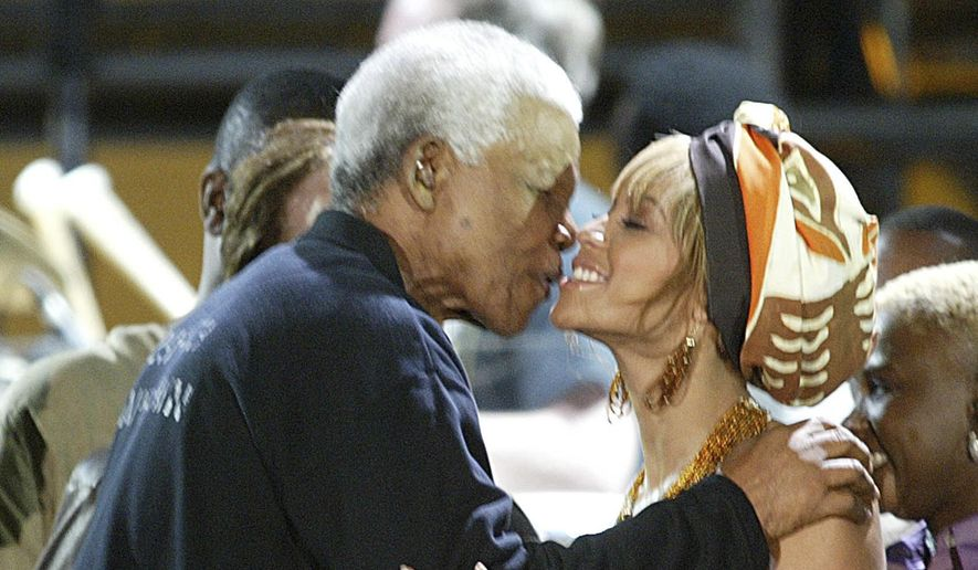 This Nov. 29, 2003, file photo shows former South African President Nelson Mandela, kissing U.S. singer Beyonce Knowles, at the Nelson Mandela AIDS Benefit Concert in Cape Town, South Africa. It is announced Monday, July 9, 2018, that Beyonce and Jay-Z will headline a special Global Citizen Festival in South Africa to honor Mandela as part of events marking the 100th anniversary of the birth of the anti-apartheid leader and Nobel Peace Prize winner. (AP Photo/file)