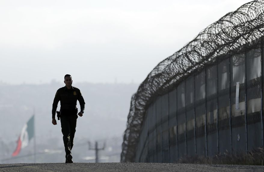 In this June 22, 2016, file photo, Border Patrol agent Eduardo Olmos walks near the secondary fence separating Tijuana, Mexico, background, and San Diego in San Diego. (AP Photo/Gregory Bull, File)