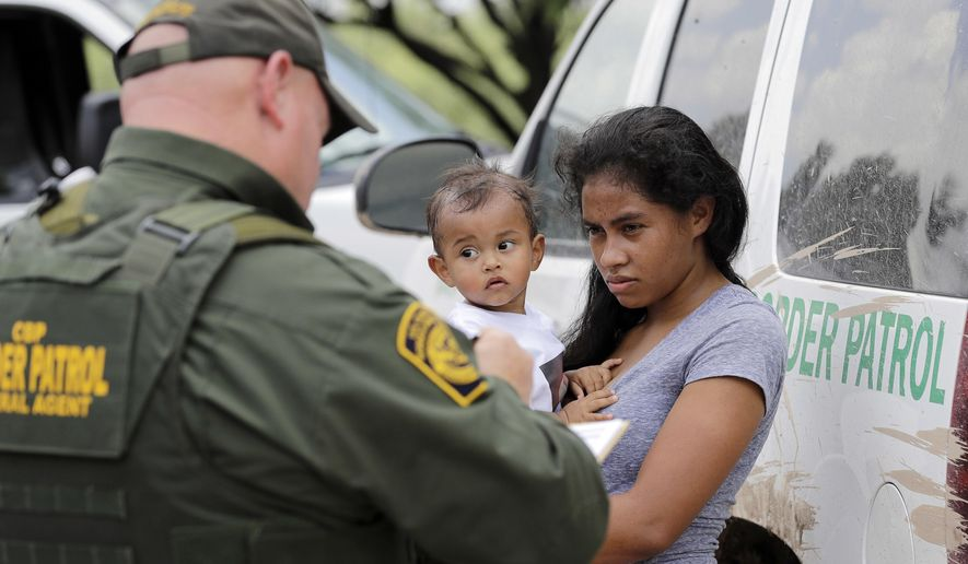 In this Monday, June 25, 2018 file photo, a mother migrating from Honduras holds her 1-year-old child as surrendering to U.S. Border Patrol agents after illegally crossing the border, near McAllen, Texas. (AP Photo/David J. Phillip, File)