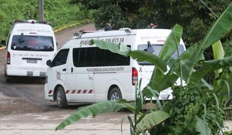 Two ambulances arrive near the cave to wait for more evacuations of the boys and their soccer coach who have been trapped since June 23, in Mae Sai, Chiang Rai province, northern Thailand Monday, July 9, 2018. Thailand's interior minister says the same divers who took part in Sunday's rescue of four boys trapped in a flooded cave will also conduct the next operation as they know the cave conditions and what to do. (AP Photo/Sakchai Lalit)