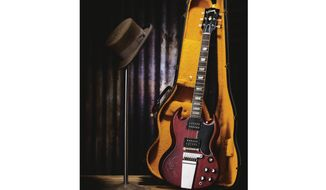 This image released by Heritage Auctions shows a top hat and a 1965 Gibson SG electric guitar owned by Tom Petty. The items will be put up for auction on July 21.. (Heritage Auctions via AP)