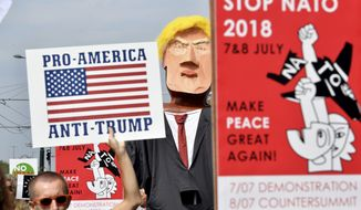 "A protester marches next to giant puppet of U.S. President Donald Trump, right, as he holds a sign that reads ""Pro-America, Anti-Trump"" during a demonstration in Brussels, Saturday, July 7, 2018. (AP Photo/Geert Vanden Wijngaert)"