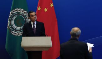 Chinese Foreign Minister Wang Yi listens to a question during a press conference after chairing the 8th Ministerial Meeting of the China-Arab States Cooperation Forum at the Diaoyutai State Guesthouse in Beijing, Tuesday, July 10, 2018. China's President Xi Jinping has pledged more than $23 billion in lines of credit, loans and humanitarian assistance to Arab countries Tuesday in a major push for influence in the region from which China sources much of its energy needs. (AP Photo/Andy Wong)