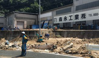 Rescuers remove the debris to clear an area hit by a mudslide caused by heavy rains in Hiroshima, southwestern Japan, Tuesday, July 10, 2018. Rescuers were combing through mud-covered hillsides and along riverbanks Tuesday searching for dozens of people missing after heavy rains unleashed flooding and mudslides in southwestern Japan. (AP Photo/Haruka Nuga)