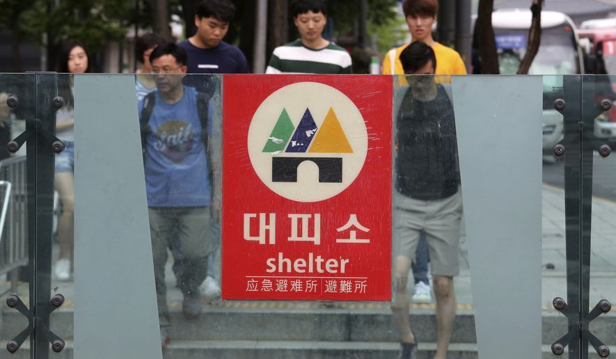 A shelter sign is displayed in the case of a possible North Korea's attacks at the entrance to a subway station in Seoul, South Korea, Tuesday, July 10, 2018. South Korea has suspended its summertime civil defense drills aimed at preparing against a North Korean attack to keep alive a positive atmosphere for nuclear diplomacy with the North. (AP Photo/Ahn Young-joon)