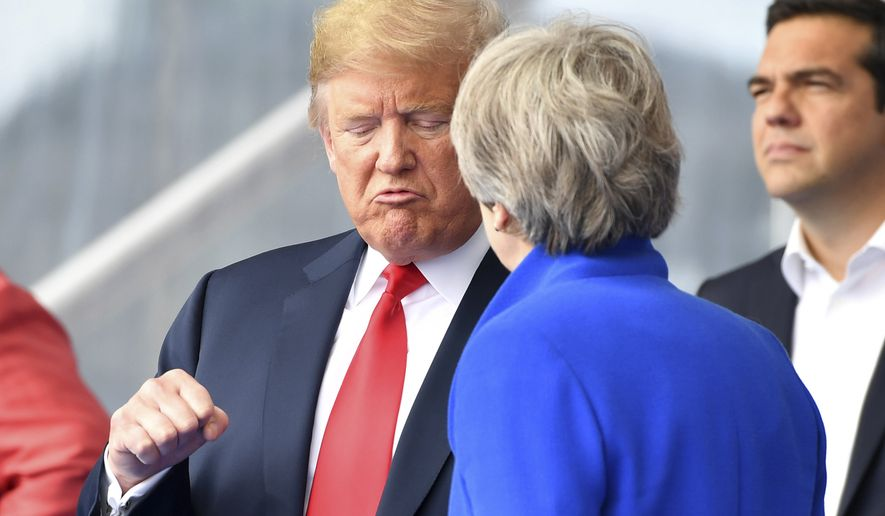 U.S. President Donald Trump, left, clenches a fist when talking to British Prime Minister Theresa May during a summit of heads of state and government at NATO headquarters in Brussels on Wednesday, July 11, 2018. NATO leaders gather in Brussels for a two-day summit to discuss Russia, Iraq and their mission in Afghanistan. (AP Photo/Geert Vanden Wijngaert)