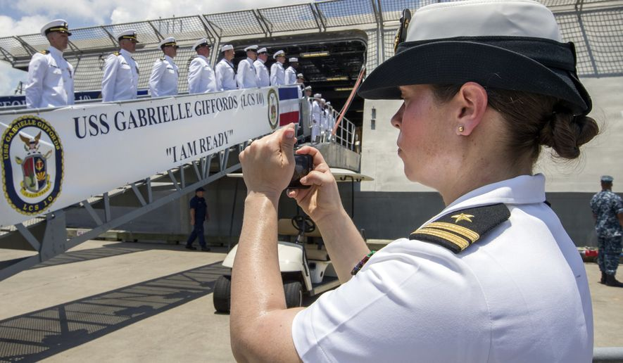 FILE - In this June 10, 2017 file photo, U.S. Navy Lt. Miranda Williams photographs sailors as they board the USS Gabrielle Giffords during a commissioning ceremony in Galveston, Texas. The Navy said Tuesday, July 10, 2018, it will let women sailors sport ponytails and other longer hairstyles, reversing a policy that long forbade females from letting their hair down. (Stuart Villanueva/The Galveston County Daily News via AP, File)