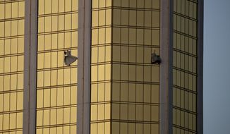 FILE - In this Oct. 2, 2017 file photo, drapes billow out of broken windows at the Mandalay Bay resort and casino on the Las Vegas Strip, following a mass shooting Oct. 1 at a music festival in Las Vegas. Aerial footage taken after the deadliest mass shooting in modern U.S. history shows the broken windows of a Las Vegas Strip casino-hotel suite where the gunman fired at a crowd gathered for a music festival. Videos released Wednesday, July 11, 2018, by police under court order also show the usually bustling Strip blocked off; runways and planes at McCarran International Airport; and officers pointing their weapons and restraining two people about a mile from the site of the shooting. (AP Photo/John Locher, File)
