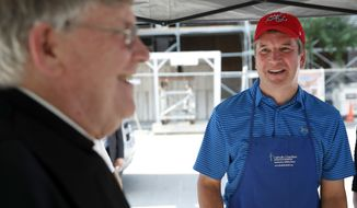 Monsignor John Enzler, left, President and CEO of Catholic Charities, Archdiocese of Washington, talks with Supreme Court nominee Brett Kavanaugh as he serves meals to the homeless as he volunteers with Catholic Charities, Wednesday, July 11, 2018 in Washington. (AP Photo/Alex Brandon)
