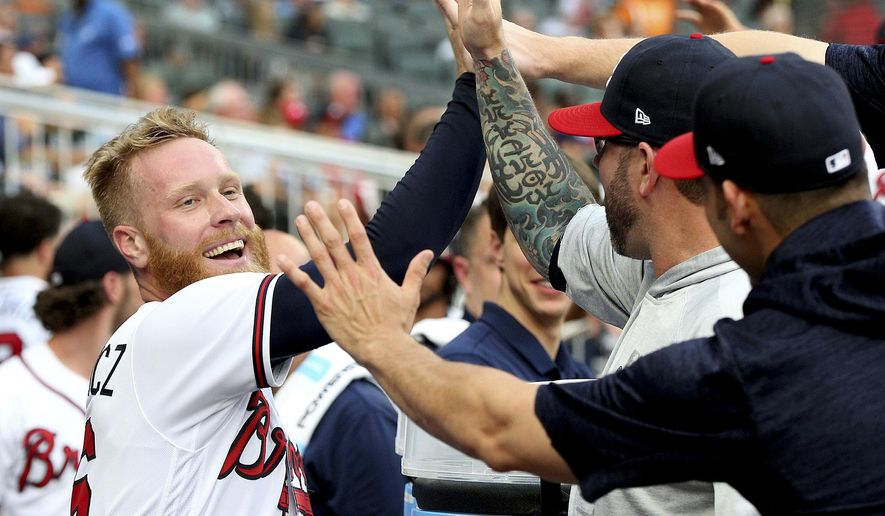 Atlanta Braves pitcher Mike Foltynewicz gets high-fives in the dugout scoring on an Ozzie Albies sacrifice fly against the Toronto Blue Jays during the second inning of a baseball game Wednesday, July 11, 2018, in Atlanta. (Curtis Compton//Atlanta Journal-Constitution via AP)