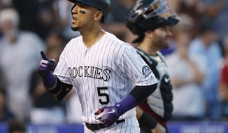Colorado Rockies' Carlos Gonzalez gestures as he crosses home plate after hitting a solo home run off Arizona Diamondbacks relief pitcher Jorge De La Rosa during the third inning of a baseball game Wednesday, July 11, 2018, in Denver. Arizona catcher Alex Avila is in back. (AP Photo/David Zalubowski)