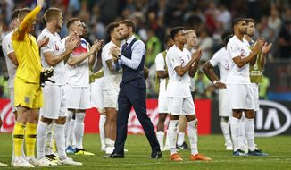 England head coach Gareth Southgate walks between his players disappointed after losing the semifinal match between Croatia and England at the 2018 soccer World Cup in the Luzhniki Stadium in Moscow, Russia, Wednesday, July 11, 2018. (AP Photo/Matthias Schrader)
