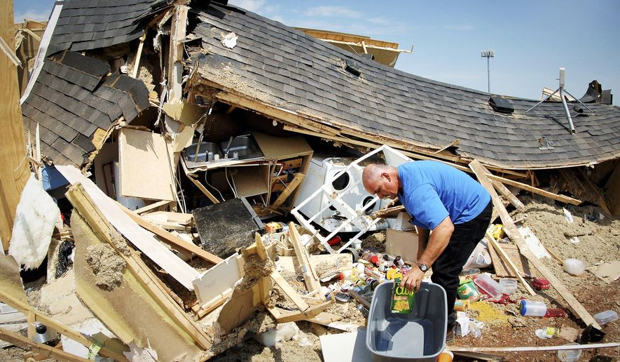 In this Tuesday, July 10, 2018 photo, Louis Vallieres searches for clothes and valuables through the wreckage of his mobile home in the Prairie View RV Park in Watford City, N.D., after a tornado whipped through the North Dakota oil patch city overnight, overturning recreational vehicles and demolishing more than 100 structures, officials said Tuesday. A newborn baby was killed and more than two dozen people were injured. (Mike McCleary/The Bismarck Tribune via AP)