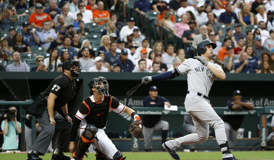 New York Yankees' Greg Bird, right, watches his grand slam in front of Baltimore Orioles catcher Caleb Joseph and home plate umpire Jim Reynolds during the third inning of a baseball game Wednesday, July 11, 2018, in Baltimore. (AP Photo/Patrick Semansky)