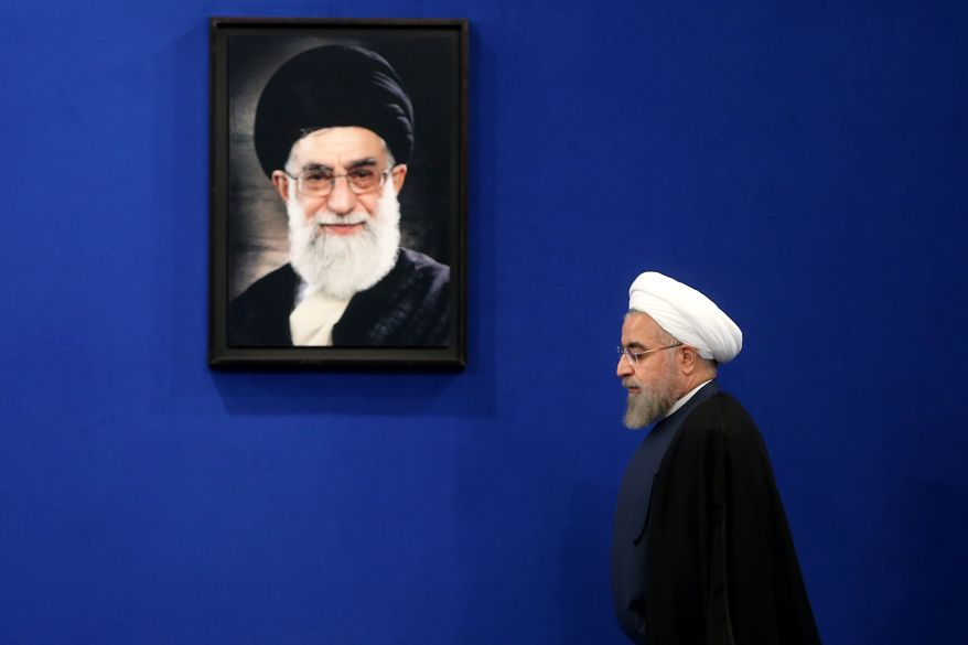 Iran's President Hassan Rouhani arrives to a press conference in Tehran, Iran, Saturday, Aug. 29, 2015. Rouhani said Saturday he opposed a parliamentary vote on the landmark nuclear deal reached with world powers, saying terms of the agreement will turn into legal obligation if it is passed by the house. Picture of the Supreme Leader Ayatollah Ali Khamenei hangs on the wall. (AP Photo/Ebrahim Noroozi)