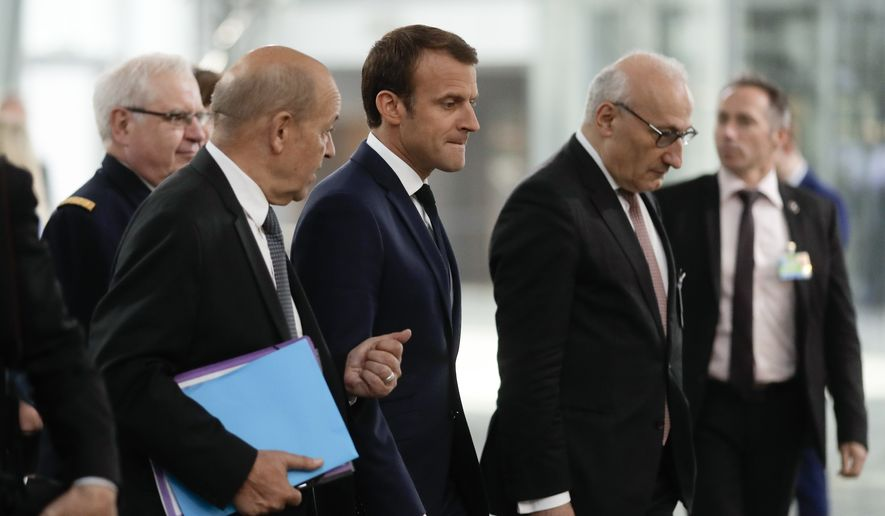 French President Emmanuel Macron, center, talks to Foreign Minister Jean-Yves Le Drian, center left, and diplomatic advisor Philippe Etienne, center right, as he walks through the NATO headquarters prior to working session of a NATO a summit of heads of state and government in Brussels on Wednesday, July 11, 2018. (AP Photo/Markus Schreiber)