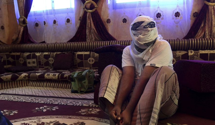 In this May 11, 2017, file photo, a former detainee covers his face for fear of being detained again, as he shows how he was kept in handcuffs and leg shackles while held in a secret prison at Riyan airport in the Yemeni city of Mukalla. In a report released Thursday, July 12, 2018, Amnesty International called for an investigation into alleged disappearances, torture and likely deaths in detention facilities in southern Yemen as possible war crimes.  (AP Photo/Maad El Zikry, File)