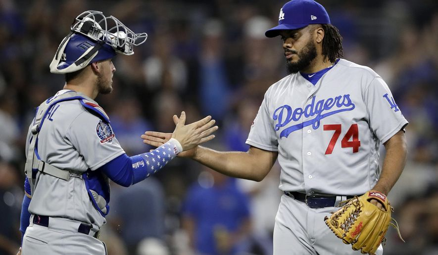 Los Angeles Dodgers relief pitcher Kenley Jansen (74) celebrates with catcher Yasmani Grandal after defeating the San Diego Padres in a baseball game Wednesday, July 11, 2018, in San Diego. The Dodgers won 4-2. (AP Photo/Gregory Bull)
