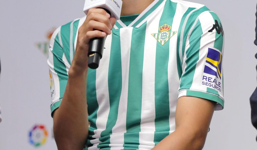 Japan's Takashi Inui speaks wearing Real Betis' shirt as he received from the team's Business General Manager Ramon Alarcon, at the Spanish embassy in Tokyo Thursday, July 12, 2018.  Inui has signed a contract with the Seville-based club until 2021, after he spent three seasons at Betis' La Liga rivals Eibar. (Kyodo News via AP)