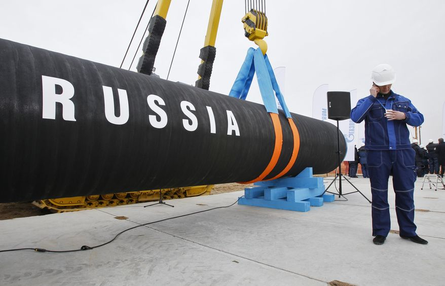 "In this April 9, 2010, photo a Russian construction worker speaks on a mobile phone in Portovaya Bay some 170 km (106 miles) north-west from St. Petersburg, Russia, during a ceremony marking the start of Nord Stream pipeline construction. In a combative start to his NATO visit, President Donald Trump asserted Wednesday that a pipeline project has made Germany ""totally controlled"" by and ""captive to Russia"" and blasted NATO allies' defense spending, opening what was expected to be a fraught summit with a list of grievances involving American allies. (AP Photo/Dmitry Lovetsky) **FILE**"