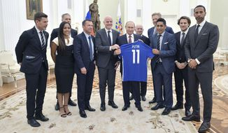 Russian President Vladimir Putin, center right, and FIFA President Gianni Infantino, center left, pose for a photo with world soccer legends during a meeting in the Kremlin in Moscow, Russia, Friday, July 6, 2018. (Alexei Druzhinin, Sputnik, Kremlin Pool Photo via AP)