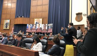 Democratic staffers hold up photos of individuals who have pleaded guilty in the Mueller Russian-collusion probe prior to the beginning of congressional testimony by FBI agent Peter Strzok on July 12, 2018. (Jeff Mordock/The Washington Times)