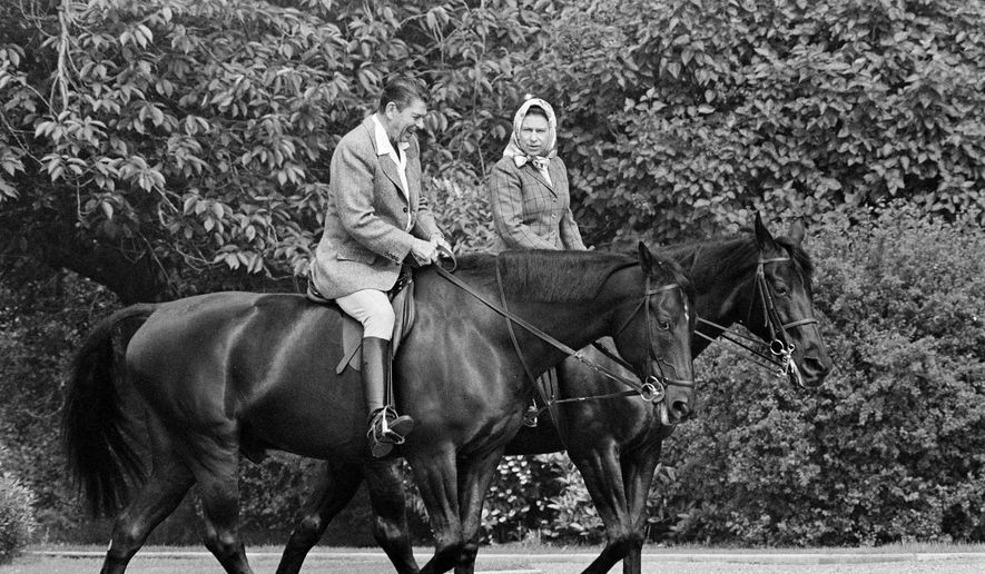 In this June 8, 1982, file photo, U.S. President Ronald Reagan, on Centennial, and Britain's Queen Elizabeth II, on Burmese, go horseback riding in the grounds of Windsor Castle, England. (AP Photo/Bob Daugherty, File)