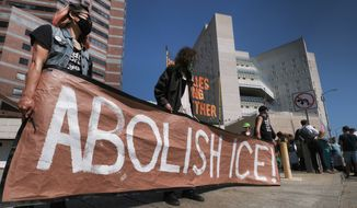 "Protesters display a sign that reads ""Abolish ICE"" during a rally in front of the Immigration and Customs Enforcement facility in downtown Los Angeles on Monday, July 2, 2018. Protesters who were blocking the entrance to an Immigration and Customs Enforcement facility in downtown Los Angeles have been led away in handcuffs. A group of 17 protesters sat down in the street, blocking the entrance to the facility Monday morning. The protesters, including faith and community leaders, locked arms and chanted, ""Shut down ICE!"" (AP Photo/Richard Vogel)"