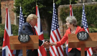 President Donald Trump, left, and British Prime Minister Theresa May, right, shake hands during their joint news conference at Chequers, in Buckinghamshire, England, Friday, July 13, 2018. (AP Photo/Pablo Martinez Monsivais)
