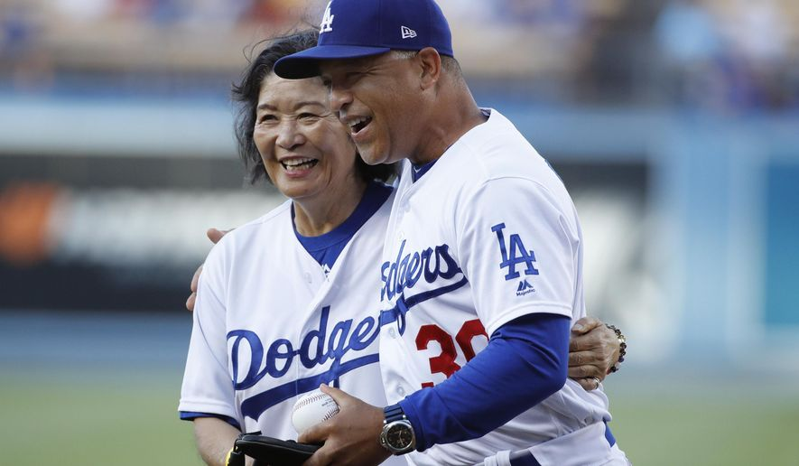 Eiko Roberts, left, is hugged by her son, Los Angeles Dodgers manager Dave Roberts, after throwing the ceremonial first pitch before a baseball game against the Los Angeles Angels, Friday, July 13, 2018, in Los Angeles. (AP Photo/Jae C. Hong)