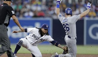 San Diego Padres shortstop Freddy Galvis, left, tags out the Los Angeles Dodgers' Chase Utley on a steal attempt during the third inning of a baseball game Thursday, July 12, 2018, in San Diego. (AP Photo/Gregory Bull)