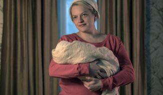 """This image released by Hulu shows Elisabeth Moss in a scene from """"The Handmaid's Tale."""" Moss was nominated Thursday for an Emmy for outstanding lead actress in a drama series. The 70th Emmy Awards will be held on Monday, Sept. 17.  (George Kraychyk/Hulu via AP)"""