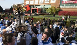 FILE - In this Nov. 26, 2016, file photo, Kentucky players hoists the Governor's Cup in front of Papa John's Cardinal Stadium after they defeated Louisville, 41-38, in an NCAA college football game, in Louisville, Ky. Papa John's, which has featured founder John Schnatter as the face of the company in logos and TV ads, is pulling his image from its marketing after reports he used a racial slur. The fallout from his comments continued Friday, July 14 2018. The University of Louisville said it will remove the Papa John's name from its football stadium, and that it will rename the John H. Schnatter Center for Free Enterprise at its business college (Jonathan Palmer/Lexington Herald-Leader via AP, File)