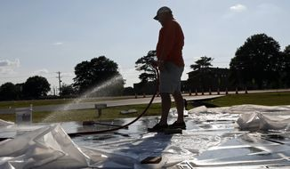 Mark Coward of Columbus Marble Works, cleans the surface of the Itta Bena, Miss., memorial, Thursday, July 12, 2018, built in honor of the 15 Marines and Navy corpsman who died in the July 10, 2017 air crash.  Several family and friends are expected to attend the Saturday, July 14, 2018 unveiling of a memorial near the crash site, built in their honor. (AP Photo/Rogelio V. Solis)