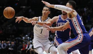 FILE - In this Oct. 11, 2017, file photo, Brooklyn Nets guard Jeremy Lin (7) passes the ball as Philadelphia 76ers guards Ben Simmons, right, and JJ Redick (17) defend during the third quarter of a preseason NBA basketball game in Uniondale, N.Y. A person with knowledge of the details says the Nets have agreed to trade Lin to the Atlanta Hawks. The Nets made the move to ease an overcrowded point guard spot early Friday morning, July 13, 2018, the person told The Associated Press on condition of anonymity because the trade had not been announced. (AP Photo/Julie Jacobson, File)