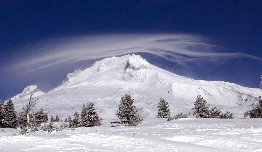 FILE - In this Dec. 13, 2009, file photo, a cloud forms over Mount Hood as seen from Government Camp, Ore.An Oregon official said a climber being rescued Friday, July 13, 2018, from Mount Hood had gone to the summit because he wanted to end his life there and that the man changed his mind when he got to the top. (AP Photo/Don Ryan, File)